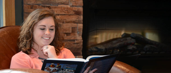 Adult female reading book by fireplace